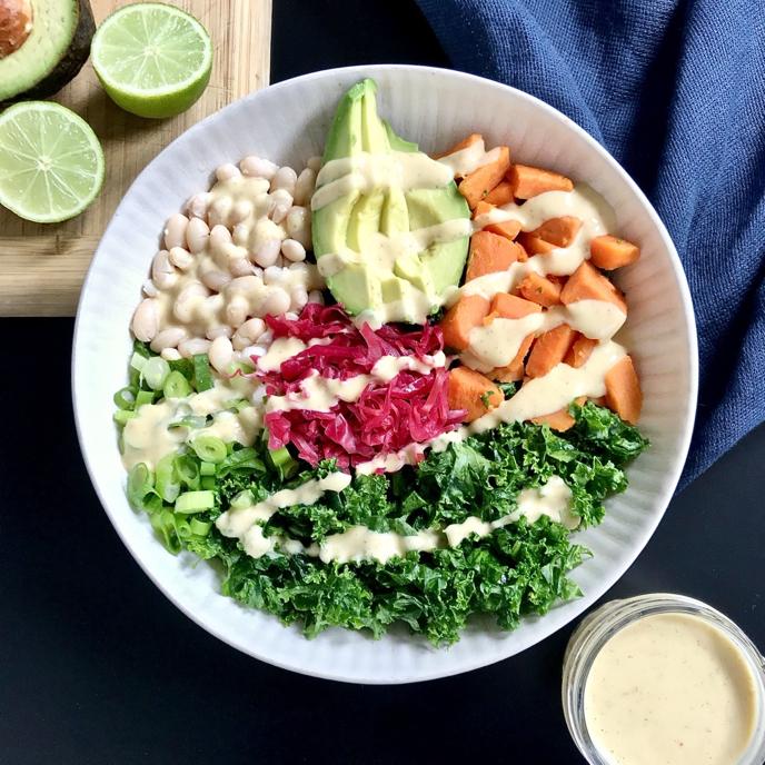 Kale, Sweet Potato, White Bean, Avocado, and Kraut Bowl with Lime Maple-Mustard MisoSauce