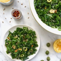 Lemony Kale Salad with Olives, Golden Raisins, Parmesan, and Sunflower Seeds